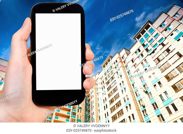 travel concept - hand holds smartphone with cut out screen and new apartment houses on background