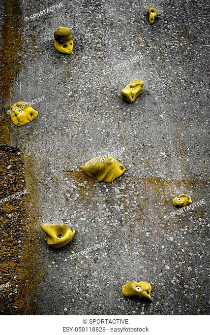 Climbing wall with yellow handles on concrete in vertical alignment reaching for the top
