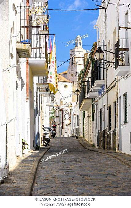 Whitewashed old town buildings along a cobbled street looking towards the Church of Santa Maria, Cadaqués, Catalonia, Spain