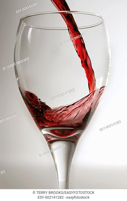 Red wine being poured into a clean wine glass against a grey backround