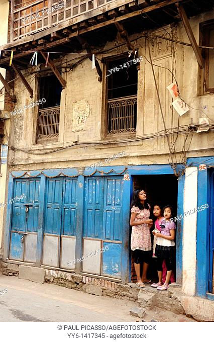 girls standing by old house in kathmandu, nepal