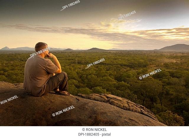 A Young Man Sitting On A Rock And Looking At The Landscape, Manica, Mozambique, Africa