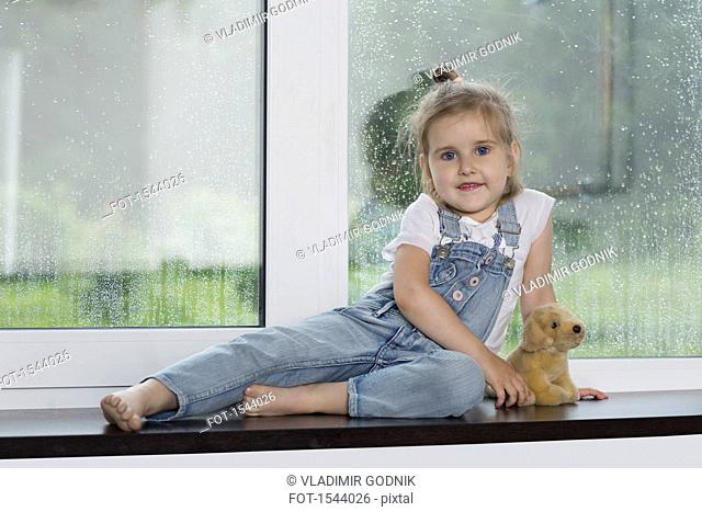 Portrait of cute smiling girl sitting with stuffed toy on window sill at home