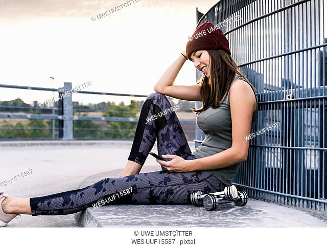 Young woman sitting on ground after dumbbell training, using smartphone