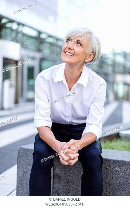 Smiling senior businesswoman sitting outside looking up
