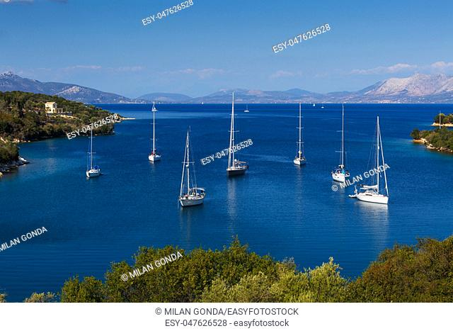 Sailboats in one of numerous small bays of Meganisi island, Greece.