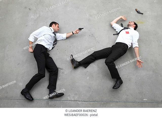 Two businessmen duelling with weapons, portrait, elevated view