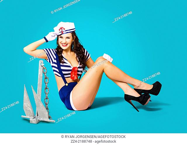 Gorgeous pin up sailor girl wearing hat saluting in navy blue style next to anchor in a maritime conceptual