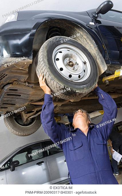 Auto mechanic working on a car wheel in a garage