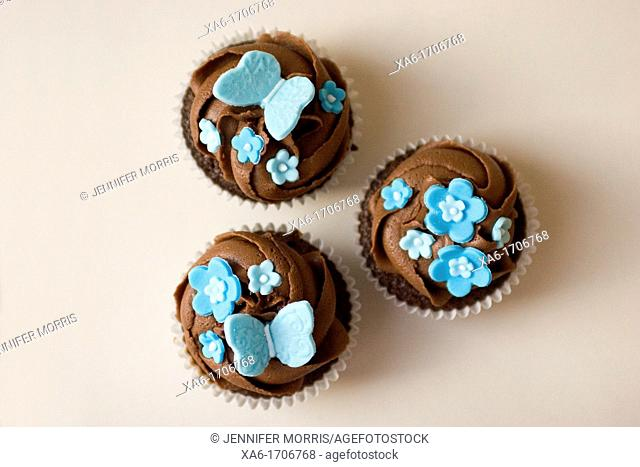 Three cupcakes with chocolate frosting swirl and blue butterfly and flower decorations on