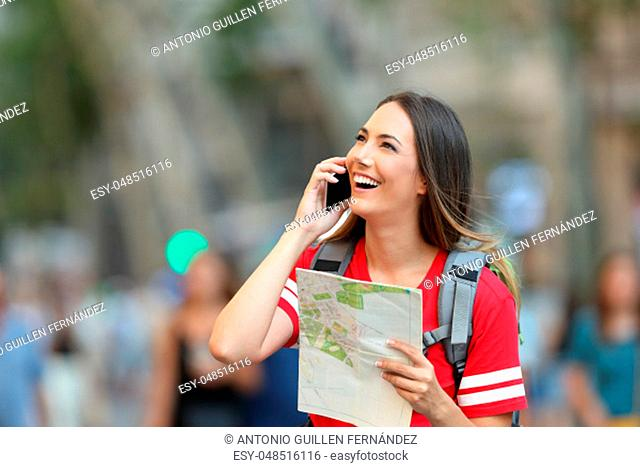 Happy teen tourist calling on phone in the street and looking above