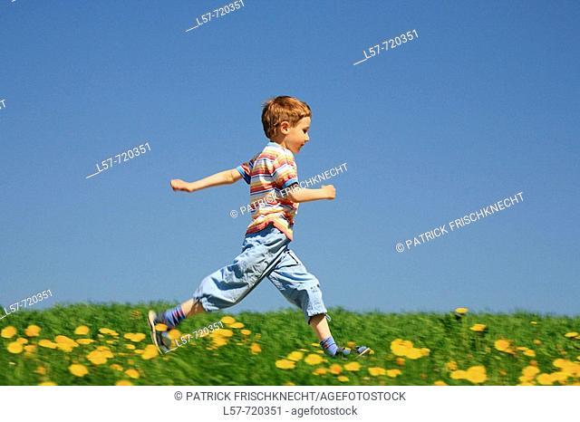 Boy running through filed of Dandelions, in spring, Switzerland