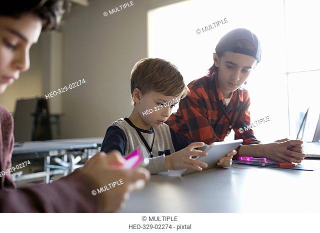 Pre-adolescent boys using digital tablet in classroom