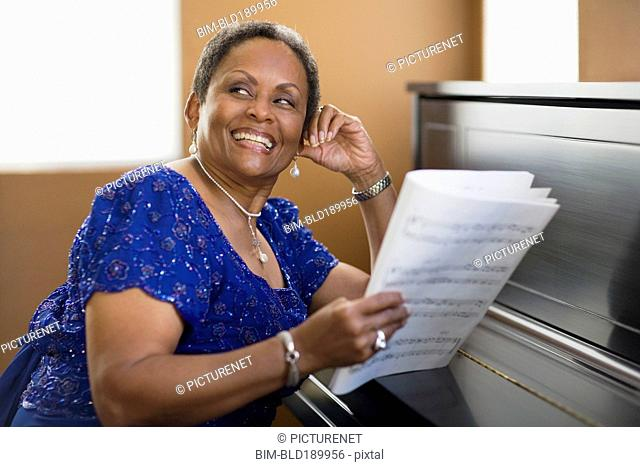 African woman leaning on closed piano