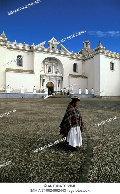 A Bolivian woman walks in the yard of the temple Copacabana, Bolivia, South America