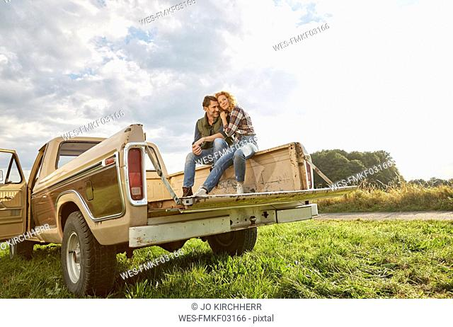 Couple sitting on pick up truck