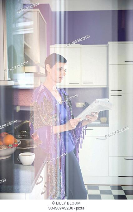 Woman reading papers in kitchen