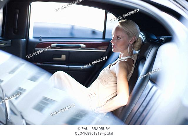 Woman sitting in backseat of limo