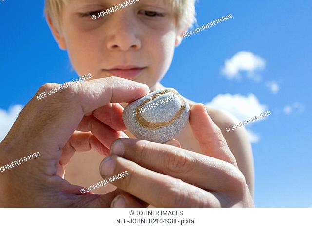 Hand holding rock, boy on background