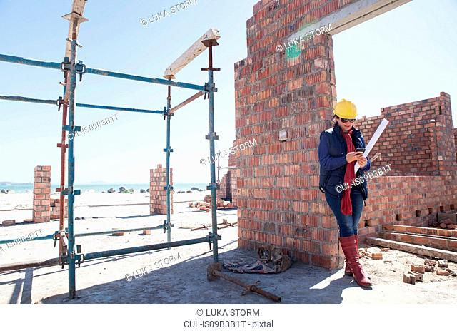 Site manager looking at blueprint on construction site