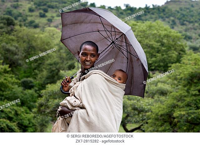 Local woman in Tis Isat or Blue Nile waterfalls, Bahar Dar, Ethiopia, Africa. Portrait of a mother next to her son at the foot of the Blue Nile Falls (Abay...