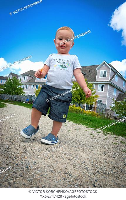 Toddler walking on a gravel path in suburban area