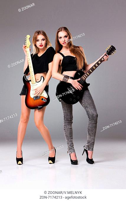 Two beautiful girls playing guitars