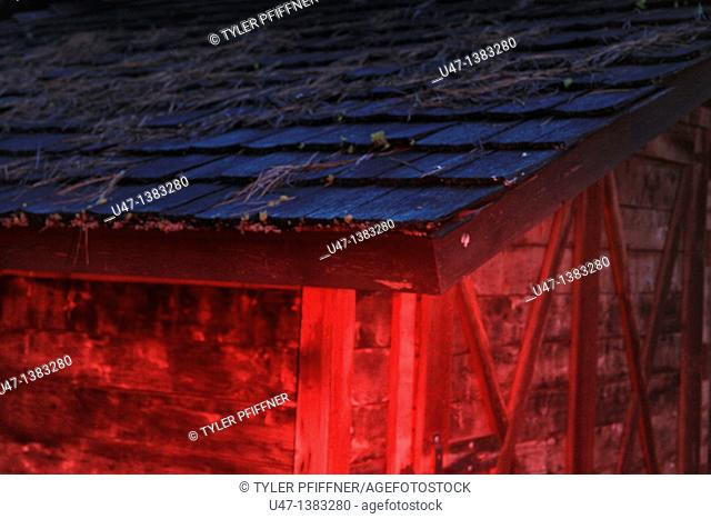 a picture of a barn roof in the evening light with red light added
