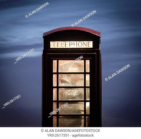 Man making call from red telephone box at night. England, United Kingdom