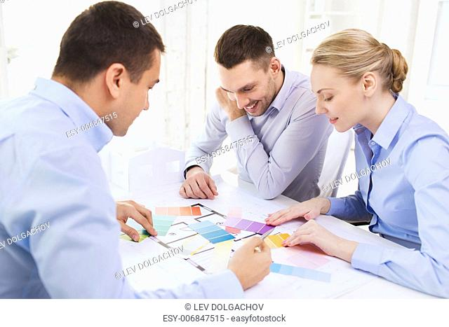 technology, education, interior design and office concept - smiling interior designers with color samples, blueprint and tablet pc in office