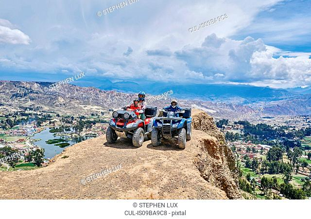 Mother and sons on top of mountain, using quad bikes, La Paz, Bolivia, South America
