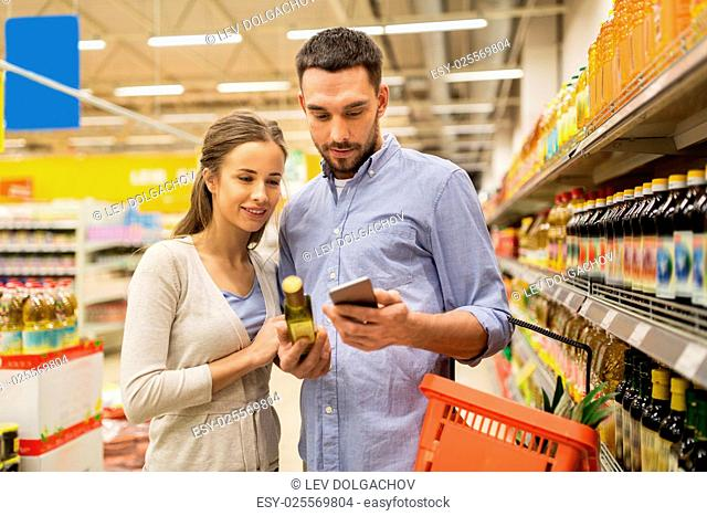 shopping, food, sale, consumerism and people concept - happy couple with smartphone buying olive oil at grocery store or supermarket