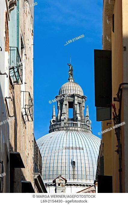Dome of Basilica Santa Maria della Salute, view strough narrow street, Sestiere Dorsoduro, Venice, Veneto, Italy