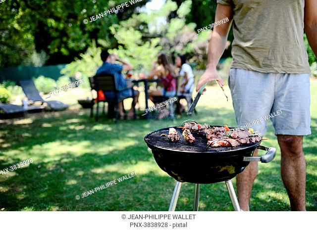 Close up of a barbecue grill with meat and sausages cooking during a summer garden party with people in background