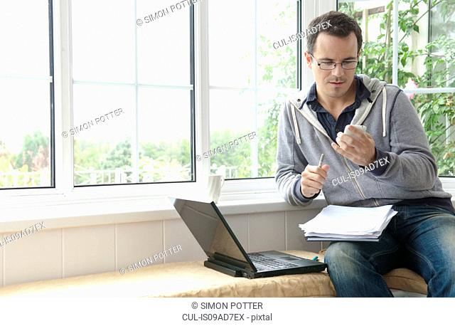 Mid adult man using mobile phone sitting in window seat