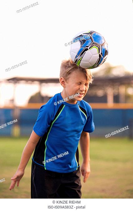 Boy with eyes closed heading football on practice pitch