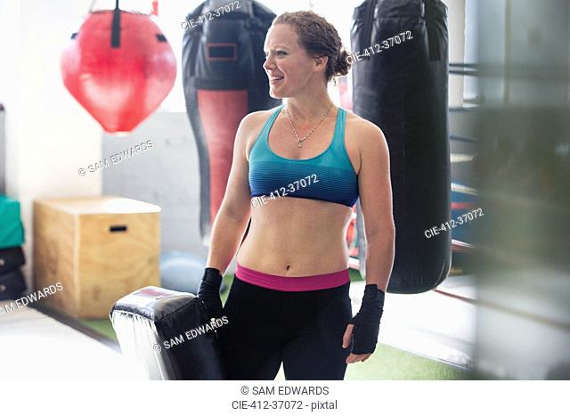 Smiling female boxer standing next to punching bag in gym