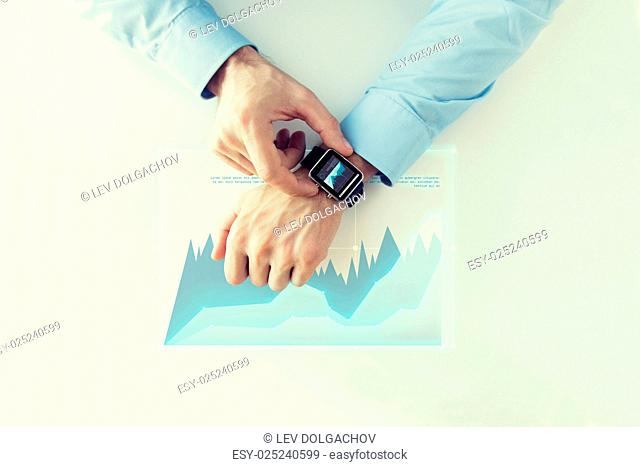 business, future technology and people concept - close up of male hands setting smart watch with virtual chart projection