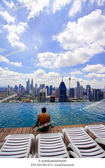 A traveller sitting on rooftop swimming pool watching Kuala Lumpur skyline view
