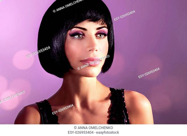 Fashion portrait of a beautiful woman over purple background, attractive model with gorgeous bob haircut and bright makeup, luxury retro look