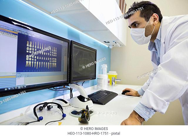 Dentist in surgical mask reviewing tooth x-rays
