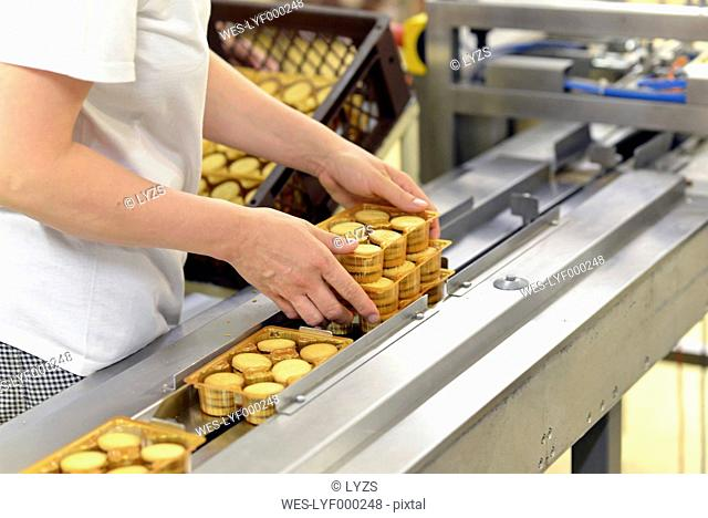 Germany, Saxony-Anhalt, woman taking pack of cookies from production line in a baking factory, partial view