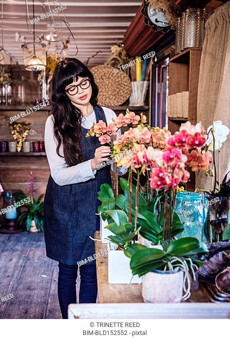 Mixed race florist arranging flowers in shop