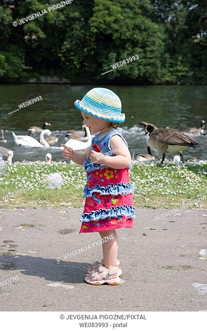 16 month old girl is walking along the Thameside Promenade  Reading  Berkshire  England