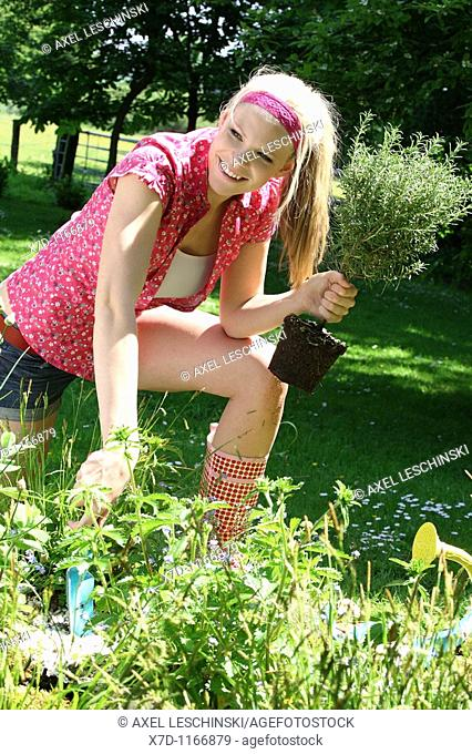 Young blond woman working in the garden