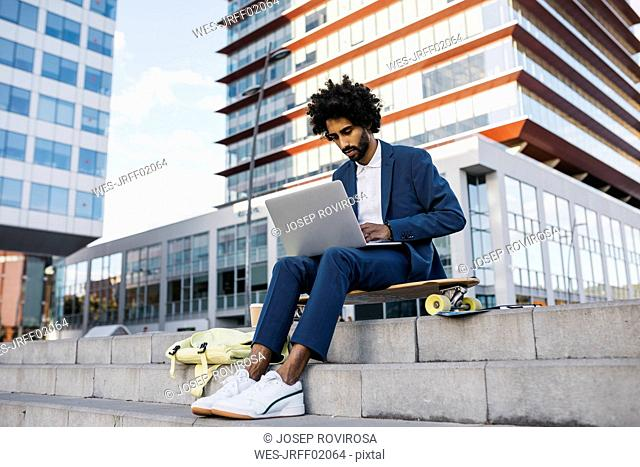 Spain, Barcelona, young businessman sitting outdoors in the city working on laptop