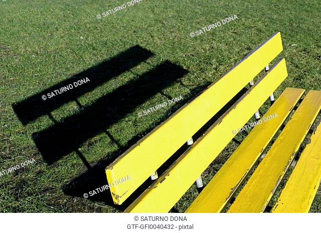 Yellow bench with its shadow in the lawn