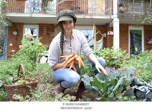 Young woman with carrots in vegetable garden