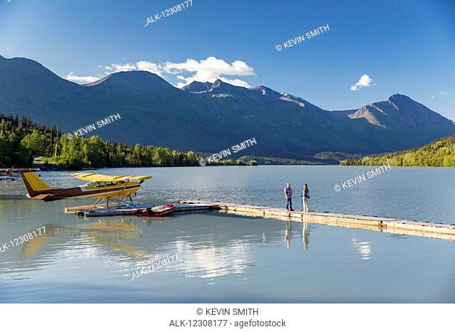 A woman and a man stand on a dock where a float plane is docked, Trail Lake Float Plane Base, Moose Pass, Kenai Peninsula, Southcentral Alaska, USA
