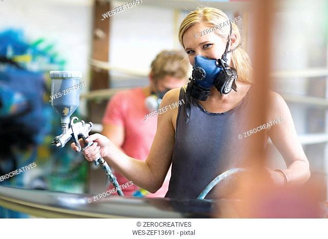 Surfboard shaper workshop, surfshop employee wearing protective mask spraying surfboard